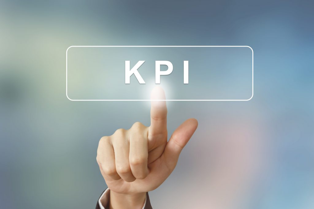 hand clicking KPI or Key Performance Indicator button on blurred