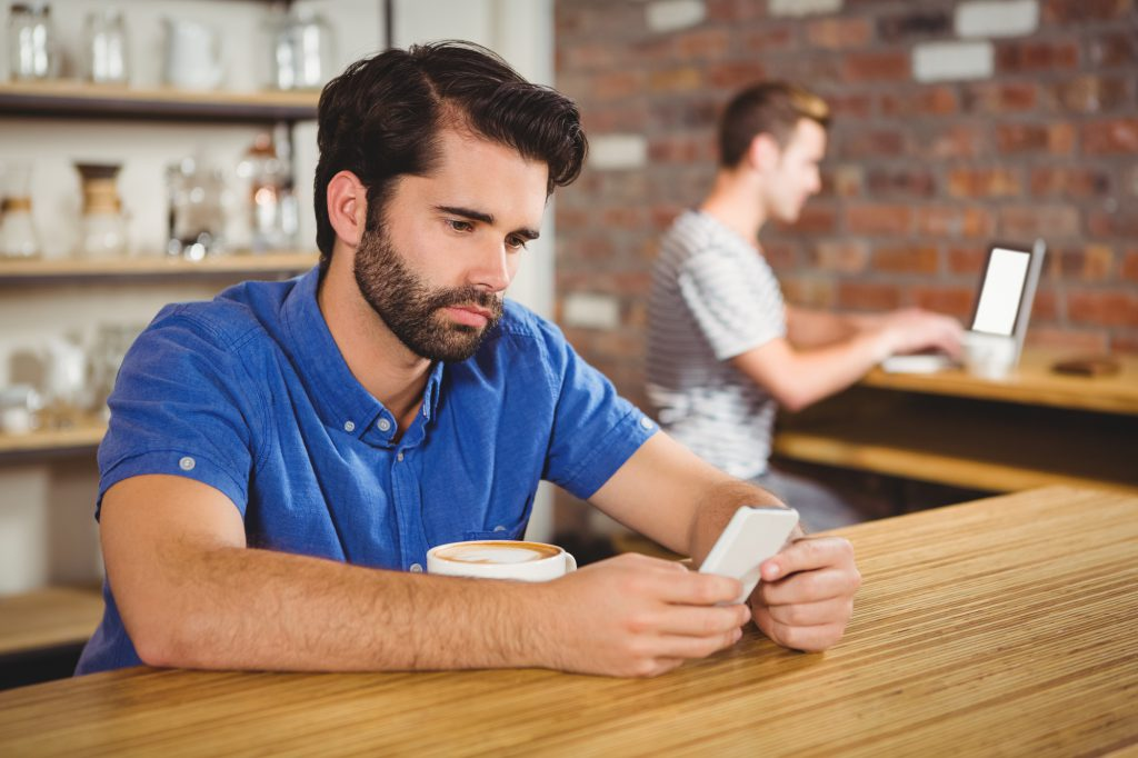 Young man using his tablet in cafe