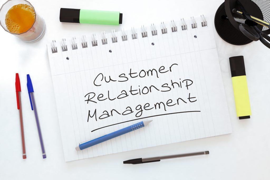 Customer Relationship Management - handwritten text in a notebook on a desk - 3d render illustration.
